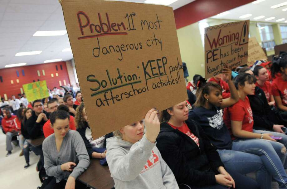 Schenectady High School tenth grade student and volleyball player Erin Center holds up a sign during a Schenectady school board meeting on Saturday April 5, 2014 in Schenectady, N.Y. Schenectady High School students were out in force on Saturday morning to protest the school boarda€™s proposed elimination of the districta€™s sports programs. (Michael P. Farrell/Times Union) Photo: Michael P. Farrell / 00026387A