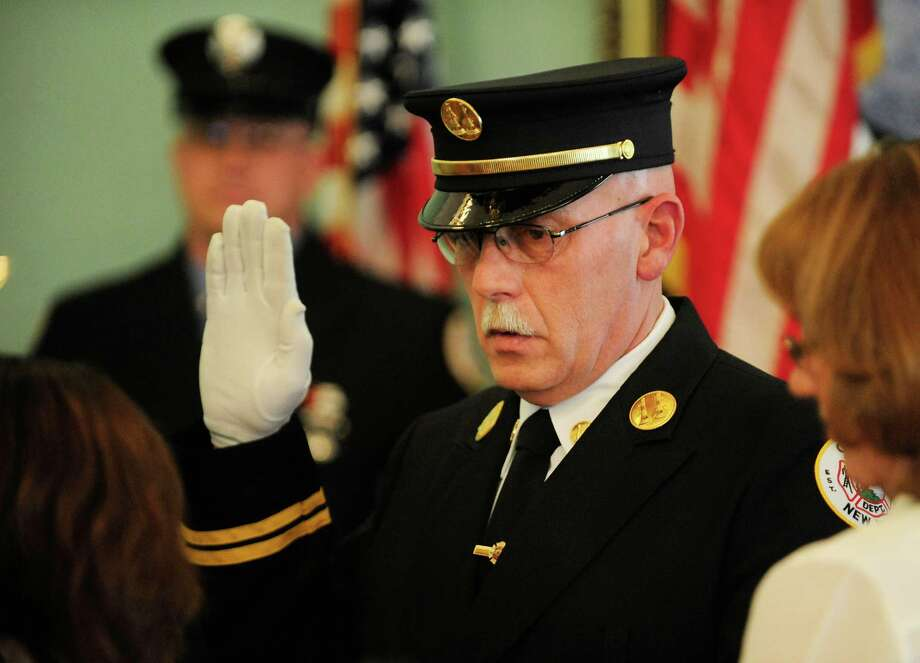 Cohoes firefighter Otto Madsen is sworn in as a captain during a promotions ceremony Wednesday morning, April 2, 2014, at the Cohoes Common Council Chambers in Cohoes, N.Y.  (Paul Buckowski / Times Union) Photo: Paul Buckowski / 00026332A