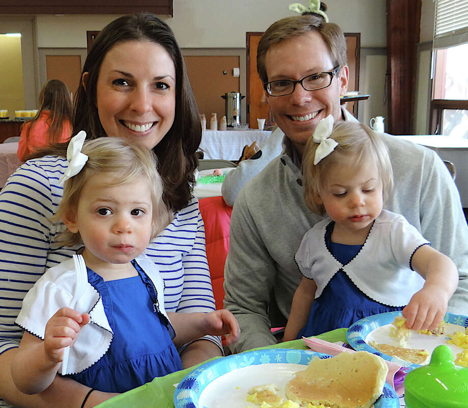 Bill and Jessica Santaniello of Fairfield enjoy a family meal with their 2-year-old twin daughters, Caroline and Allison, at Fairfield Grace Church's Easter Bunny Pancake Breakfast on Saturday morning. Photo: Mike Lauterborn / Fairfield Citizen