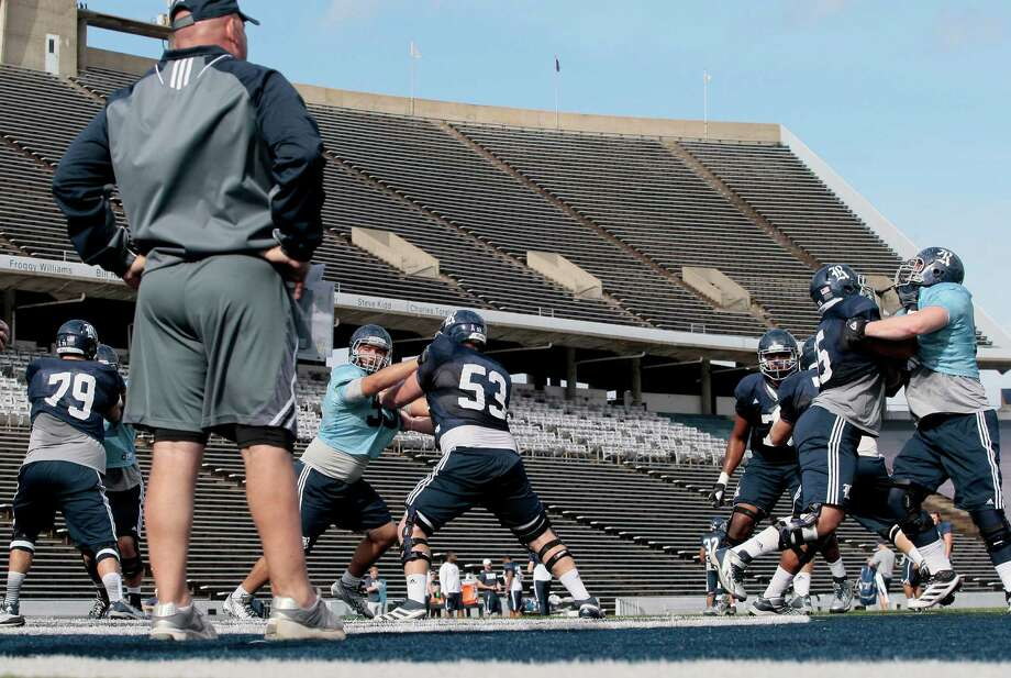 Rice University offensive line coach Ronnie Vinklarek watched his offensive line run through drills during practice at Rice Stadium in December. The decision to allow scholarship football players at Northwestern University to unionize could affect athletes at Rice. Photo: Thomas B. Shea, Freelance / © 2013 Thomas B. Shea