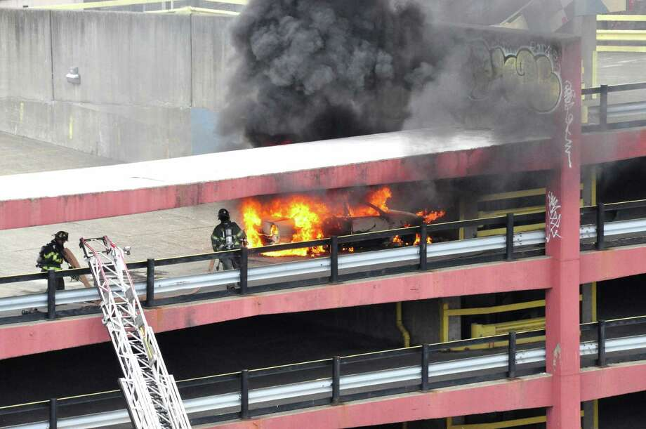 City firefighters respond to a burning car on top of the parking deck above Capital Repertory Theatre on North Pearl Street around 3 p.m. Saturday. (Steve Barnes / Times Union)