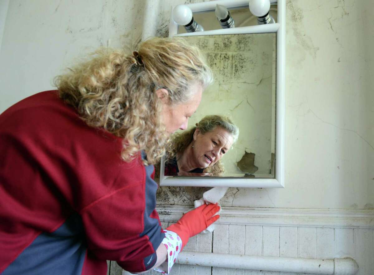 Mary Newman-Clark wipes away years of grime at the house on the grounds of the former American Shakespeare Theatre in Stratford, Conn. Saturday, April 5, 2014. Newman-Clark, who lives across the street from the house, volunteered her time to help refurbish it for The Shakespeare Academy @ Stratford, a summer acting program for college students that will be starting there in July. The house cleanup and the summer academy is being organized by the Mighty Quinn Foundation, named for 19-year-old Quinn Rooney, who loved acting and Shakespearean plays.