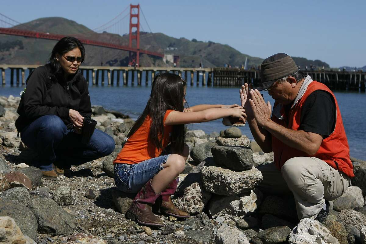 Mel Omega (left) watches her daughter Elliot Lansender, 6, (center) stack rocks with the help of Bill Dan (right) on Crissy Field at the Presidio on April 5, 2014 in San Francisco, Calif. Dan has been stacking rocks at Crissy Field for 20 years.
