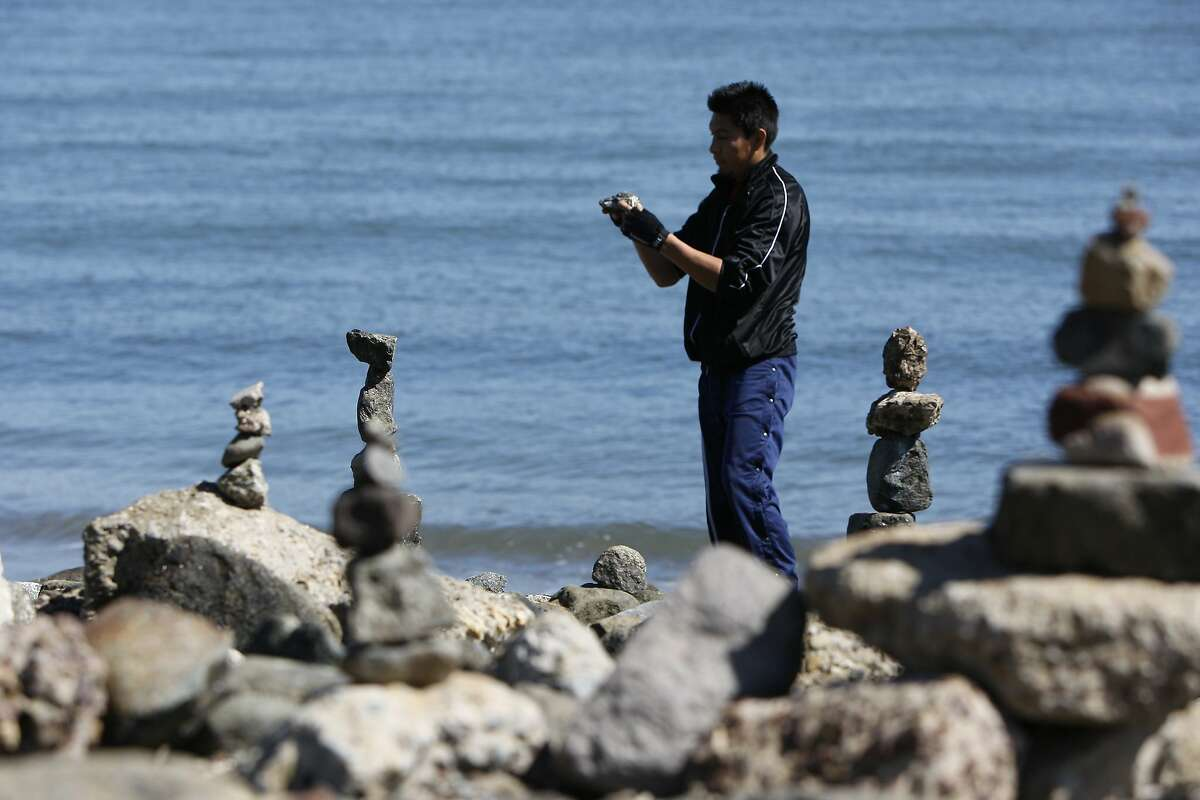 Gregorio Calva examines a rock before adding it to his stack on Crissy Field at the Presidio on April 5, 2014 in San Francisco, Calif. Bill Dan and Zach Pine (not pictured) hold rock stacking events on Crissy Field where people are welcome to stop by and learn how to do it.