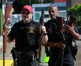 Police officers Warren Lee (left) and Raphael Rockwell carry rifles that were turned in by a gun owner at a gun buyback program in San Francisco.