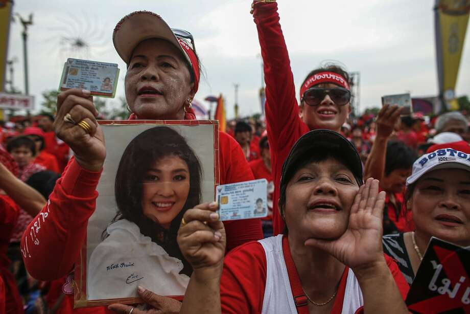 A pro-government Red Shirt member holds a photo of Prime Minister Yingluck Shinawatra at a rally on the outskirts of Bangkok to counter months of protests against the government. Photo: Athit Perawongmetha, Reuters