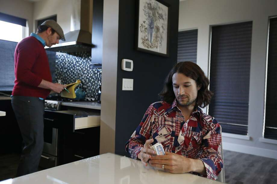 Charlie Craig (left) and Dave Mullins prepare to play cards at their home in Westminster, Colo. The couple turned to Facebook when a local bakery refused to make a cake for their wedding. Photo: Brennan Linsley, Associated Press