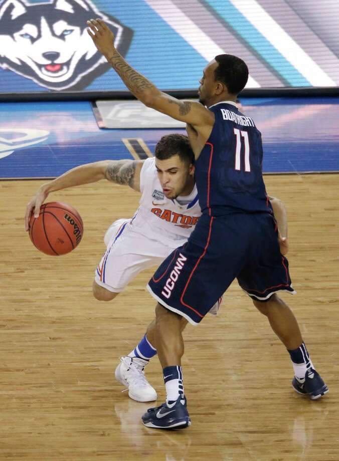 Florida guard Scottie Wilbekin, left, drives around Connecticut guard Ryan Boatright  during the first half of the NCAA Final Four tournament college basketball semifinal game Saturday, April 5, 2014, in Arlington, Texas. Photo: Tony Gutierrez, AP / Associated Press
