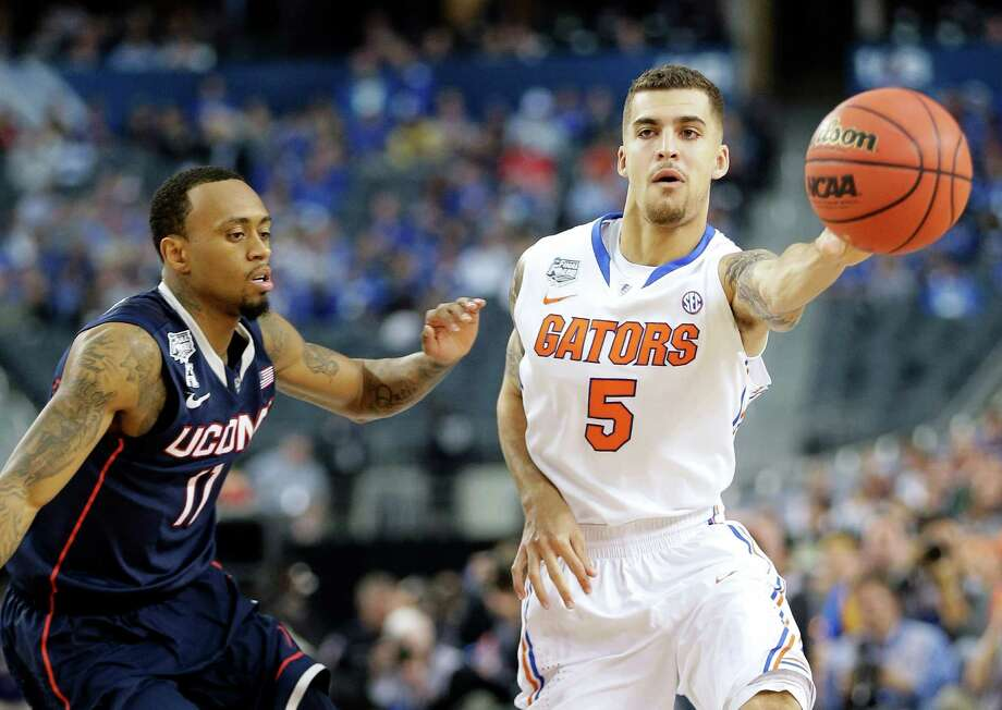 Florida guard Scottie Wilbekin (5) passes as Connecticut guard Ryan Boatright (11) defends during the first half of the NCAA Final Four tournament college basketball semifinal game Saturday, April 5, 2014, in Arlington, Texas. Photo: Eric Gay, AP / Associated Press