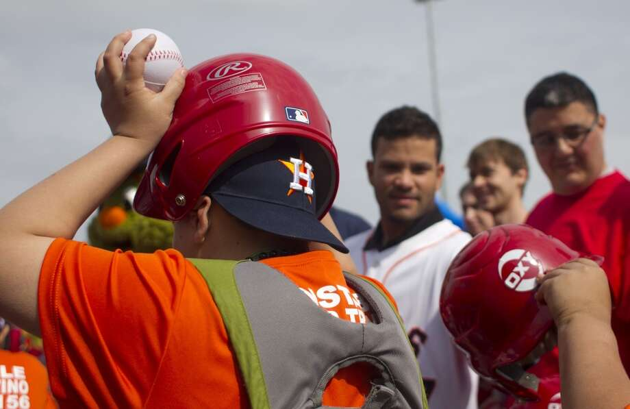A Denver Harbor Little Leaguer puts on the helmet given to him by current Astro Jose Altuve, right, at the Denver Harbor Little League's newly revitalized youth baseball fields at Denver Harbor Park. Photo: Johnny Hanson, Houston Chronicle