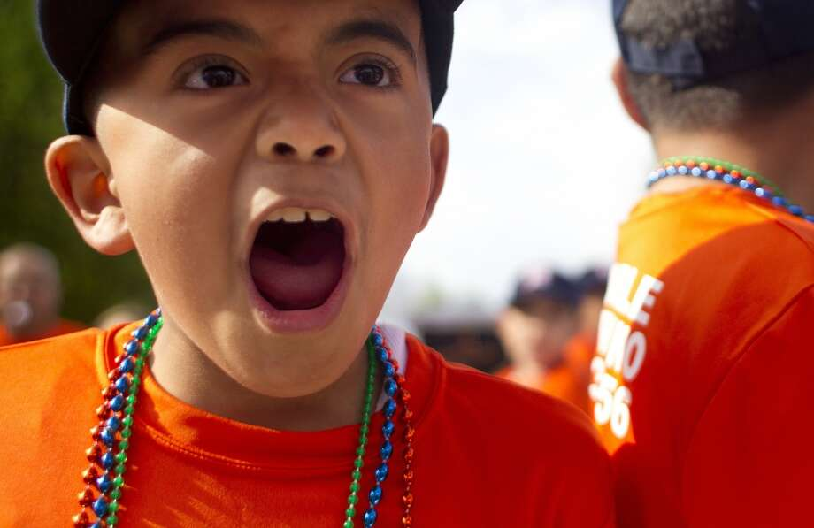 "Denver Harbor Little Leaguer, Sammy Sandoval, 7, shouts ""We are the Astros, "" while riding on his team's float during a parade celebrating their leagues newly revitalized youth baseball fields at Denver Harbor Park. Photo: Johnny Hanson, Houston Chronicle"