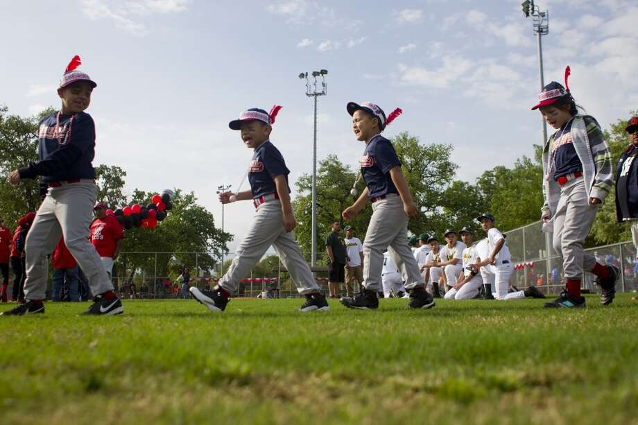"Shouting ""We are the Indians, "" a group of Denver Harbor Little Leaguers walk onto their newly revitalized youth baseball fields at Denver Harbor Park. Photo: Johnny Hanson, Houston Chronicle"