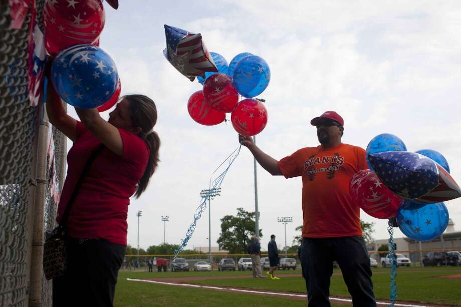 Erica and Jesse Elizondo hang balloons in preparation for the celebration of the newly revitalized Denver Harbor Little League. Photo: Johnny Hanson, Houston Chronicle