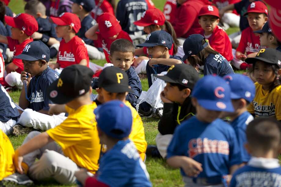 Denver Harbor Little Leaguers wait for the celebration to begin as they sat on the leagues newly revitalized youth baseball fields at Denver Harbor Park. Photo: Johnny Hanson, Houston Chronicle