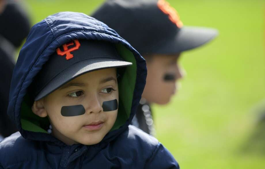 Denver Harbor Little Leaguer, Bernardo Castillo, 4, waits for the celebration to begin as he sat on the leagues newly revitalized youth baseball fields. Photo: Johnny Hanson, Houston Chronicle