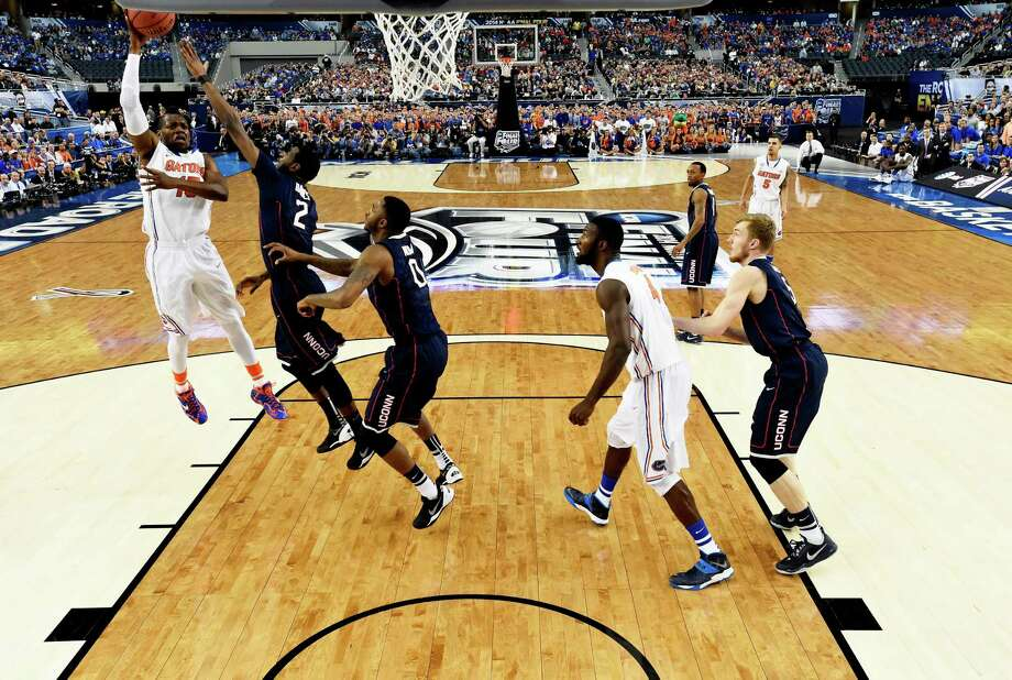 ARLINGTON, TX - APRIL 05: Will Yeguete #15 of the Florida Gators goes to the basket as DeAndre Daniels #2 of the Connecticut Huskies defends during the NCAA Men's Final Four Semifinal at AT&T Stadium on April 5, 2014 in Arlington, Texas. Photo: Pool, Getty Images / Getty Images