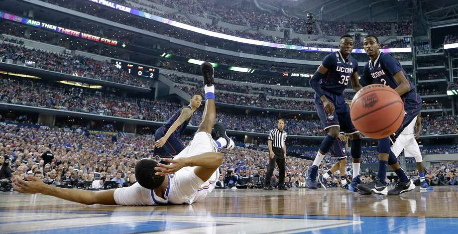 Florida guard Kasey Hill, left, falls to the court in front of Connecticut's Amida Brimah (35) and DeAndre Daniels (2) during the first half of an NCAA Final Four tournament college basketball semifinal game Saturday, April 5, 2014, in Arlington, Texas. Photo: Eric Gay, AP / Associated Press