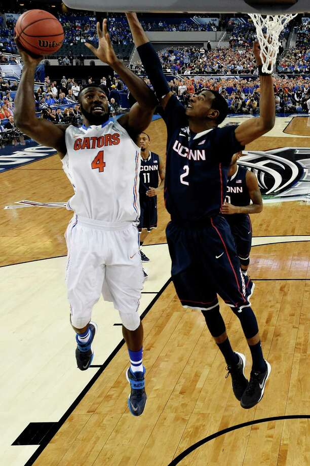 ARLINGTON, TX - APRIL 05: Patric Young #4 of the Florida Gators goes to the basket as DeAndre Daniels #2 of the Connecticut Huskies defends during the NCAA Men's Final Four Semifinal at AT&T Stadium on April 5, 2014 in Arlington, Texas. Photo: Pool, Getty Images / Getty Images