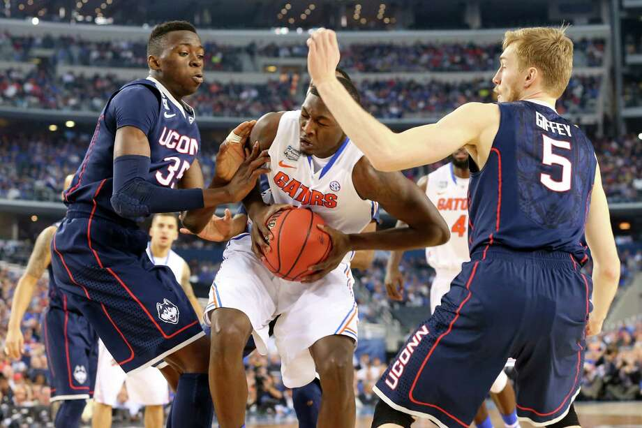 ARLINGTON, TX - APRIL 05: Dorian Finney-Smith #10 of the Florida Gators goes to the basket as Amida Brimah #35 and Niels Giffey #5 of the Connecticut Huskies defend during the NCAA Men's Final Four Semifinal at AT&T Stadium on April 5, 2014 in Arlington, Texas. Photo: Ronald Martinez, Getty Images / Getty Images