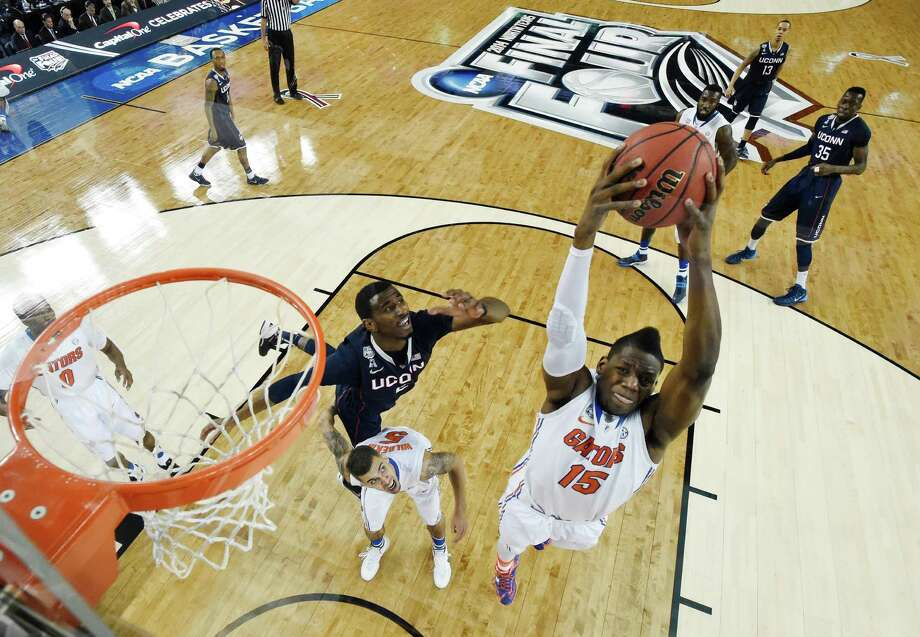 Florida forward Will Yeguete (15) grabs a rebound as Connecticut forward DeAndre Daniels (2) topples over Florida's Scottie Wilbekin (5) during the first half of the NCAA Final Four tournament college basketball semifinal game Saturday, April 5, 2014, in Dallas. Photo: Chris Steppic, AP / Associated Press