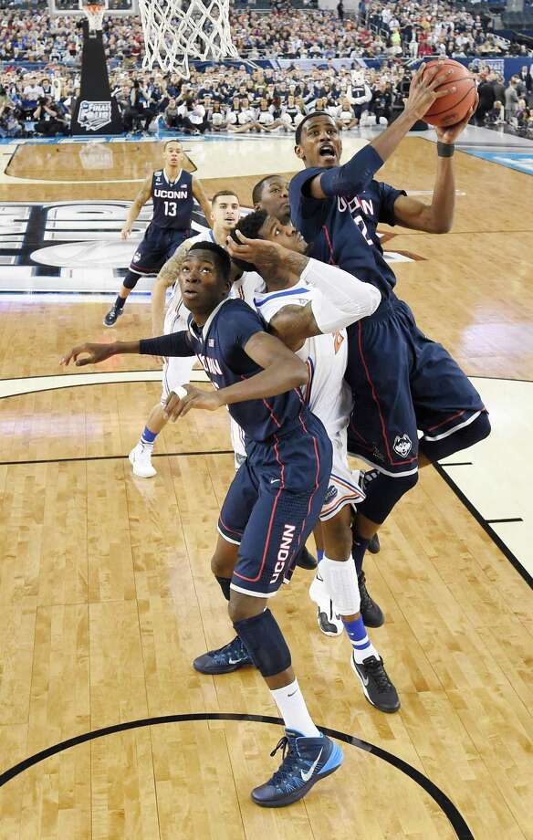 Connecticut forward DeAndre Daniels (2) shoots around defender Florida's Chris Walker (23) during the first half of the NCAA Final Four tournament college basketball semifinal game Saturday, April 5, 2014, in Arlington, Texas. Connecticut's Amida Brimah, left, holds his ground. Photo: Chris Steppic, AP / Associated Press