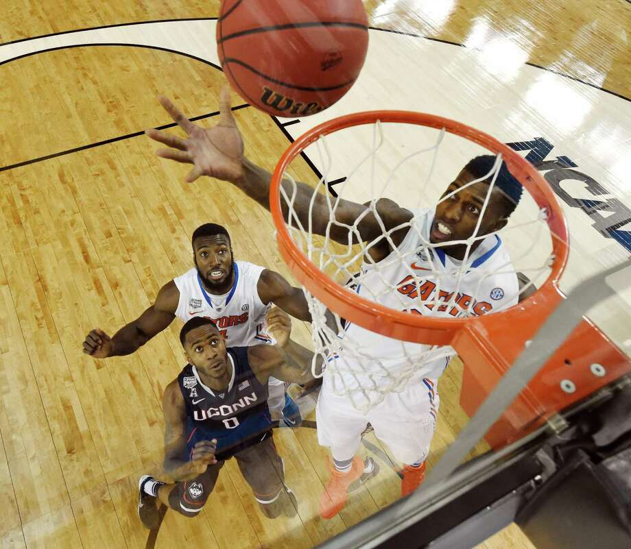 Florida forward Casey Prather shoots as Connecticut forward Phillip Nolan (0) and Florida's Patric Young (4) look on during the first half of the NCAA Final Four tournament college basketball semifinal game Saturday, April 5, 2014, in Dallas. Photo: Chris Steppic, AP / Associated Press