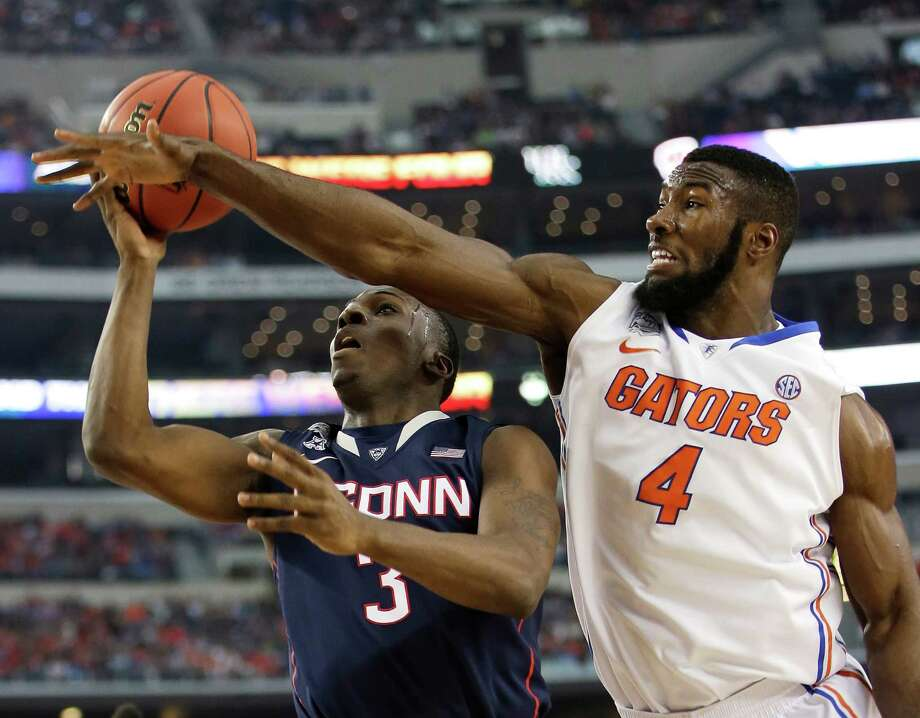Connecticut guard Terrence Samuel, left, drives to the basket past Florida center Patric Young during the first half of an NCAA Final Four tournament college basketball semifinal game Saturday, April 5, 2014, in Arlington, Texas. (AP Photo/David J. Phillip) Photo: David J. Phillip, ASSOCIATED PRESS / Associated Press
