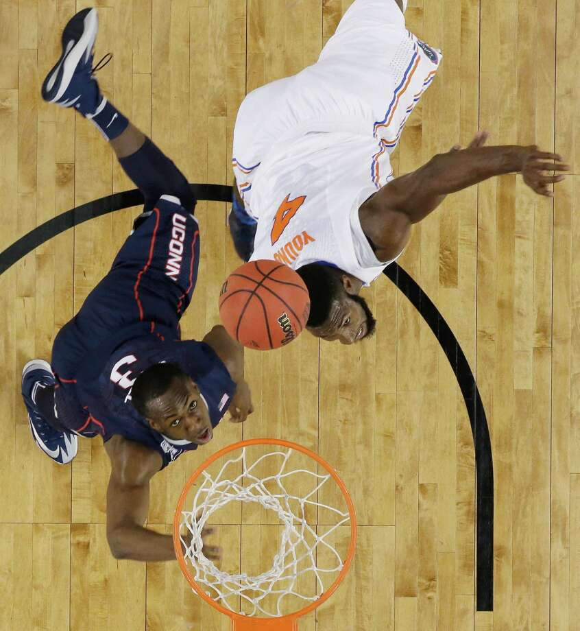 Connecticut guard Terrence Samuel, left, and Florida center Patric Young eye a rebound during the first half of an NCAA Final Four tournament college basketball semifinal game Saturday, April 5, 2014, in Arlington, Texas. Photo: David J. Phillip, AP / Associated Press
