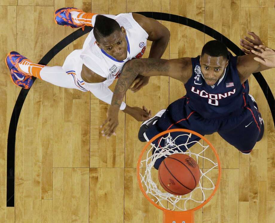 Florida forward Will Yeguete, left, and Connecticut forward Phillip Nolan, right, eye a made basket during the first half of an NCAA Final Four tournament college basketball semifinal game Saturday, April 5, 2014, in Arlington, Texas. Photo: David J. Phillip, AP / Associated Press