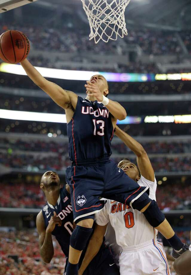 Connecticut guard Shabazz Napier (13) drives to the basket over Florida center Patric Young, right, during the first half of an NCAA Final Four tournament college basketball semifinal game Saturday, April 5, 2014, in Arlington, Texas. Photo: David J. Phillip, AP / Associated Press