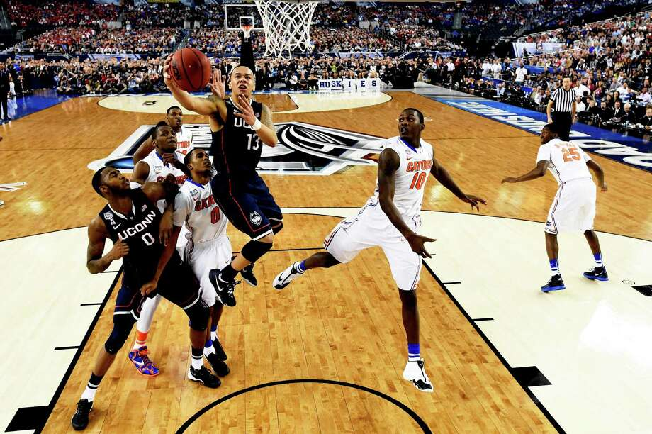 ARLINGTON, TX - APRIL 05: Shabazz Napier #13 of the Connecticut Huskies goes to the basket as Dorian Finney-Smith #10 and Kasey Hill #0 of the Florida Gators defend during the NCAA Men's Final Four Semifinal at AT&T Stadium on April 5, 2014 in Arlington, Texas. Photo: Pool, Getty Images / Getty Images