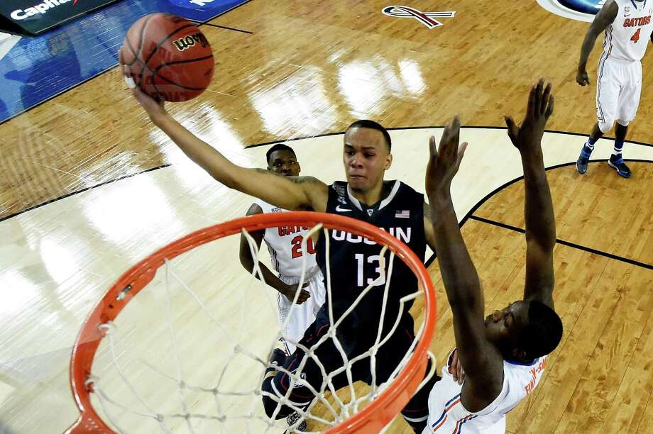 ARLINGTON, TX - APRIL 05: Shabazz Napier #13 of the Connecticut Huskies goes to the basket as Dorian Finney-Smith #10 of the Florida Gators defends during the NCAA Men's Final Four Semifinal at AT&T Stadium on April 5, 2014 in Arlington, Texas. Photo: Pool, Getty Images / Getty Images