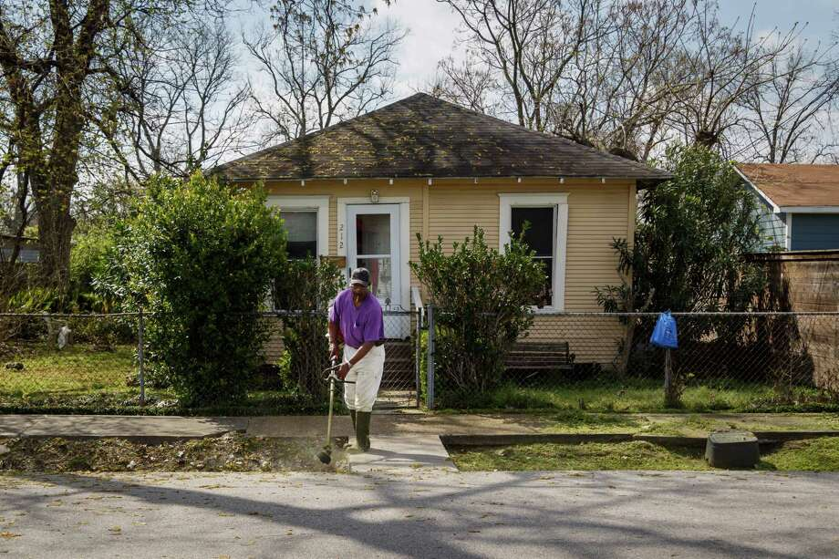 Clarance Simmons trims the grass in front of a house on 31 1/2 Street. Photo: Michael Paulsen, Houston Chronicle / © 2014 Houston Chronicle