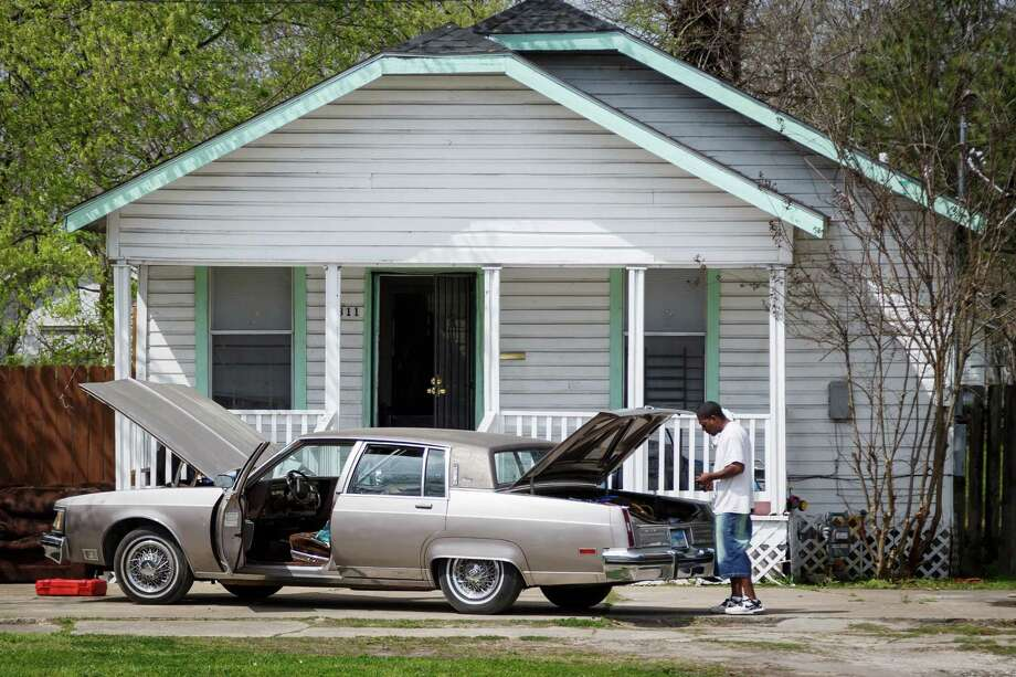 A man fixes his car along Main St. in the Independence Heights area. Photo: Michael Paulsen, Houston Chronicle / © 2014 Houston Chronicle