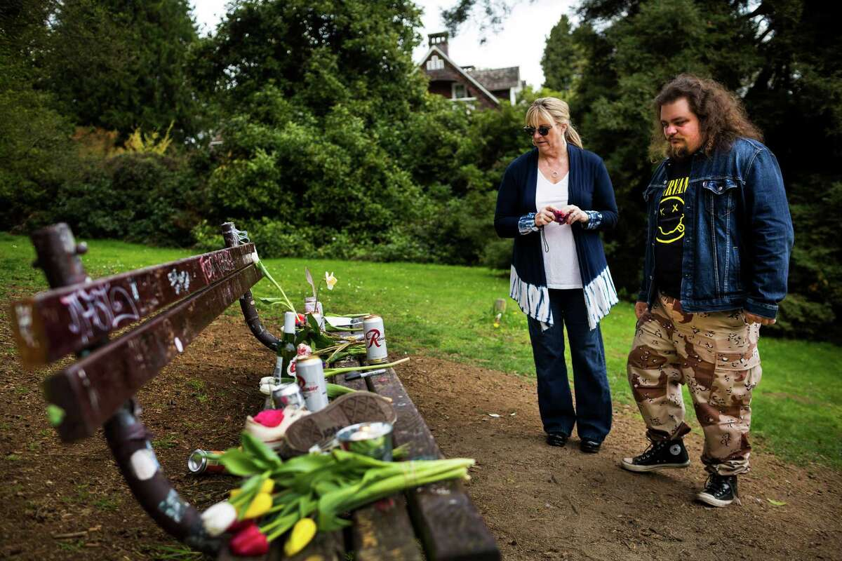 Several hundred yards from the home where Nirvana's Kurt Cobain killed himself in 1994, background, fans of the late lead singer such as Beau Allen, 27, right, and his mother, Bobbi Binder, center right, visited a bench loaded with offerings of flowers, unopened beers and handwritten notes on the 20th anniversary of Cobain's death Saturday, April 5, 2014, at Viretta Park in Seattle. Allen also visited the site on the tenth anniversary of the singer's death, and has been a fan of Nirvana since age six. On April 10, 2014, Nirvana will be inducted into the Rock and Roll Hall of Fame.