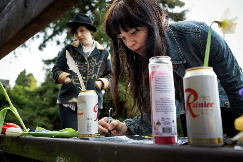 "Portland residents Ashly Archibald, 26, left, and Kim Hoffman, 28, right, scrawls the quote, ""who needs action when you have words?"" in memory of Nirvana's lead singer, Kurt Cobain, on a bench near the home where he died on the 20th anniversary of his death Saturday, April 5, 2014, at Viretta Park in Seattle. On April 10, Nirvana will be inducted into the Rock and Roll Hall of Fame. Photo: JORDAN STEAD, SEATTLEPI.COM / SEATTLEPI.COM"