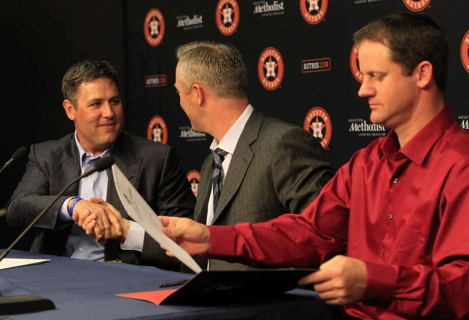 Astros President of Business Operations Reid Ryan, center, chats as Lance Berkman, left, and Roy Oswalt, right, sign a one-day contract with the Astros. Photo: Karen Warren, Houston Chronicle