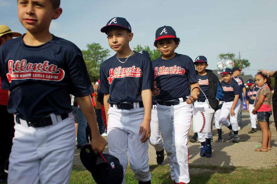 Denver Harbor Little Leaguers walk onto their newly revitalized youth baseball fields at Denver Harbor Park Saturday, April 5, 2014, in Houston. Photo: Johnny Hanson, Houston Chronicle / © 2014  Houston Chronicle
