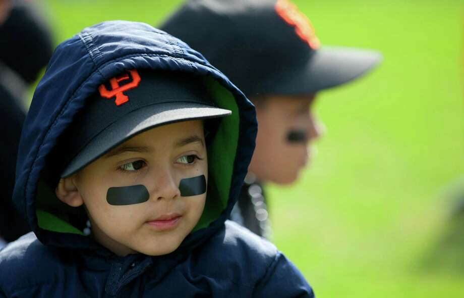 Denver Harbor Little Leaguer, Bernardo Castillo, 4, waits for the celebration to begin as he sits on the leagues newly revitalized youth baseball fields at Denver Harbor Park. Photo: Johnny Hanson, Houston Chronicle / © 2014  Houston Chronicle