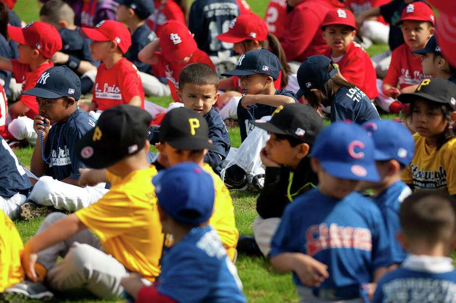 Denver Harbor Little Leaguers wait for the celebration to begin as they sat on the leagues newly revitalized youth baseball fields at Denver Harbor Park. Photo: Johnny Hanson, Houston Chronicle / © 2014  Houston Chronicle