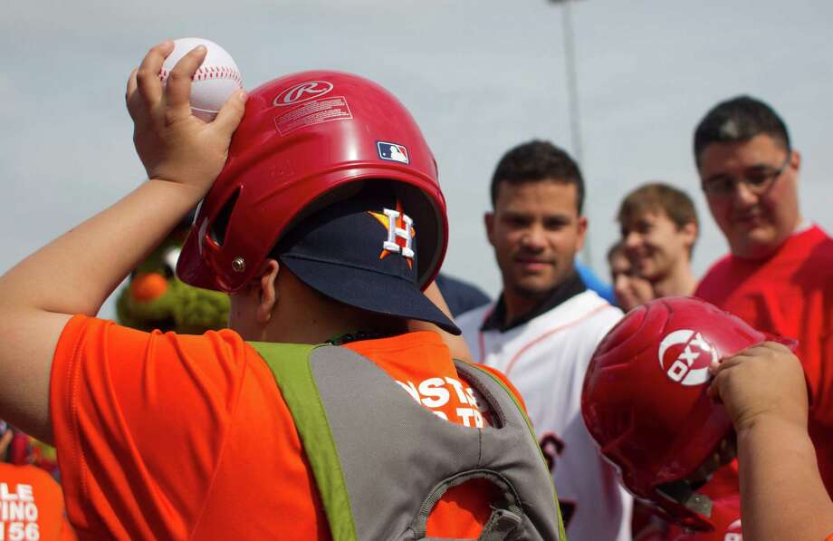 A Denver Harbor Little Leaguer puts on the helmet given to him by current Houston Astro Jose Altuve, right, at the Denver Harbor Little League's newly revitalized youth baseball fields at Denver Harbor Park. Photo: Johnny Hanson, Houston Chronicle / © 2014  Houston Chronicle