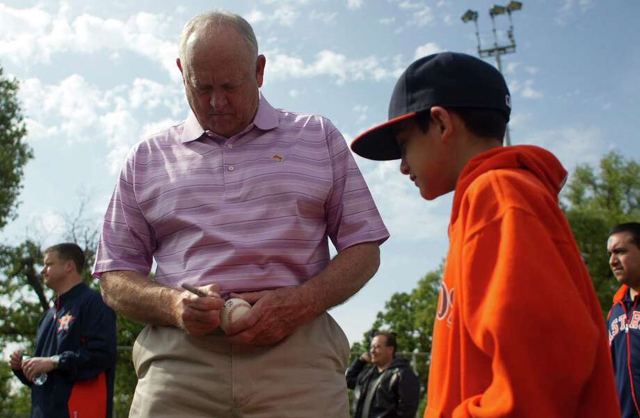Former Astro and current executive advisor, Nolan Ryan, signs a baseball for Ethan Munoz, 11, as the Denver Harbor Little Leaguers celebrated their newly revitalized youth baseball fields at Denver Harbor Park. Photo: Johnny Hanson, Houston Chronicle / © 2014  Houston Chronicle