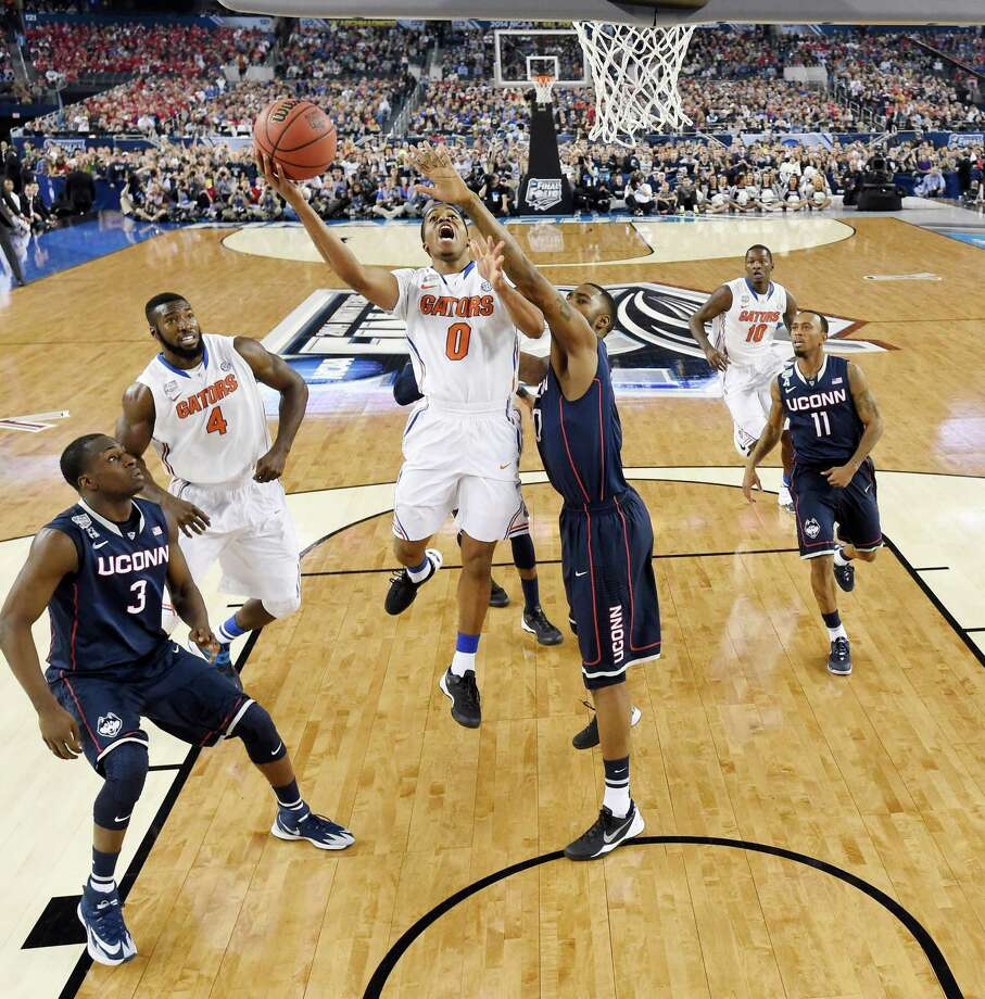 Florida guard Kasey Hill (0) shoots as Connecticut forward Phillip Nolan (0) defends during the second half of the NCAA Final Four tournament college basketball semifinal game Saturday, April 5, 2014, in Arlington, Texas. Photo: Chris Steppig, AP / Associated Press