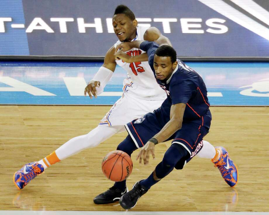 Connecticut forward DeAndre Daniels works to maintain control of the ball as Florida forward Will Yeguete (15) defends during the second half of the NCAA Final Four tournament college basketball semifinal game Saturday, April 5, 2014, in Arlington, Texas. Photo: Tony Gutierrez, AP / Associated Press
