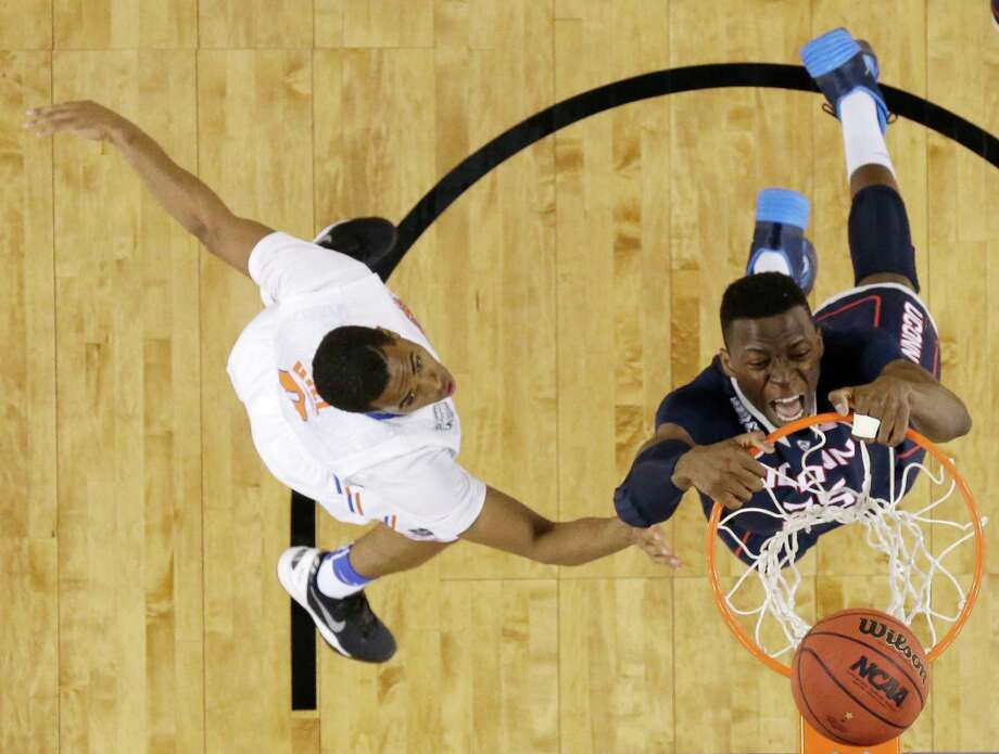 Connecticut center Amida Brimah, right, dunks the ball in front of Florida guard Kasey Hill during the second half of an NCAA Final Four tournament college basketball semifinal game Saturday, April 5, 2014, in Arlington, Texas. Photo: David J. Phillip, AP / Associated Press