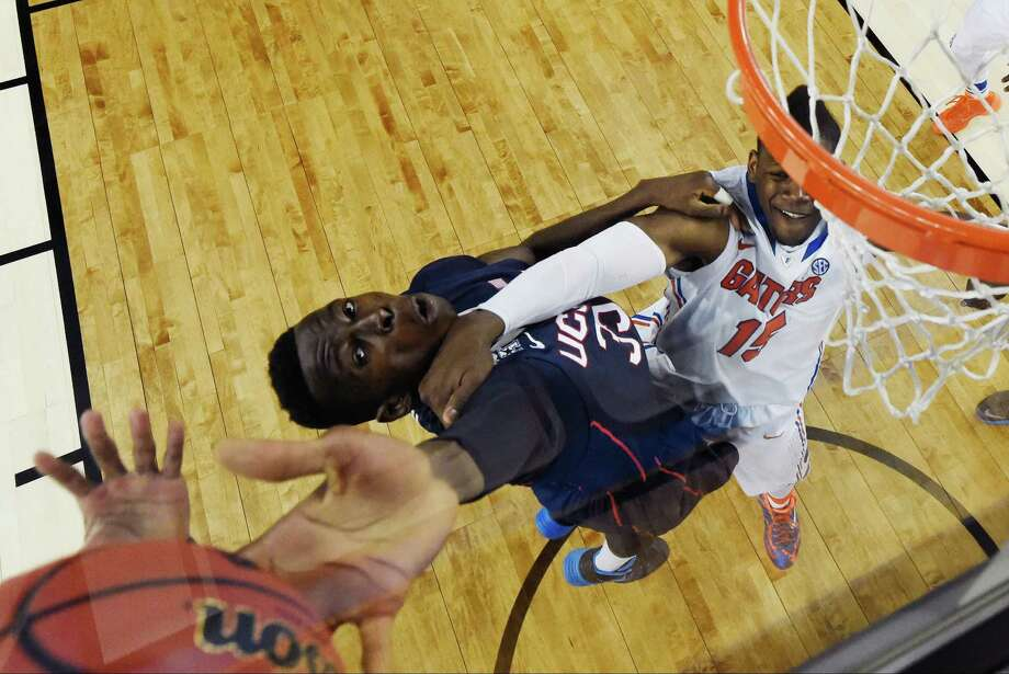 Connecticut center Amida Brimah (35) reaches for the ball as Florida forward Will Yeguete (15) defends during the second half of the NCAA Final Four tournament college basketball semifinal game Saturday, April 5, 2014, in Arlington, Texas. Photo: Chris Steppig, AP / Associated Press
