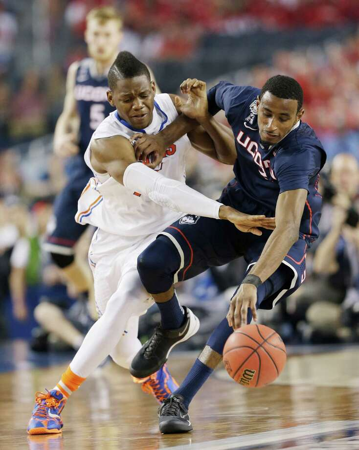 Florida forward Will Yeguete (15) reaches in against Connecticut forward DeAndre Daniels (2) during the second half of the NCAA Final Four tournament college basketball semifinal game Saturday, April 5, 2014, in Arlington, Texas. Photo: David J. Phillip, AP / Associated Press