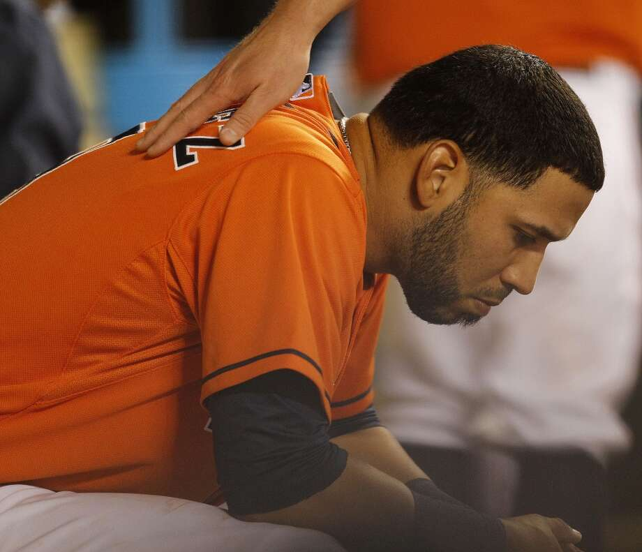 Astros shortstop Marwin Gonzalez is patted on the back by a teammate as he takes a moment between innings in the dugout after striking out with bases loaded. Photo: Karen Warren, Houston Chronicle