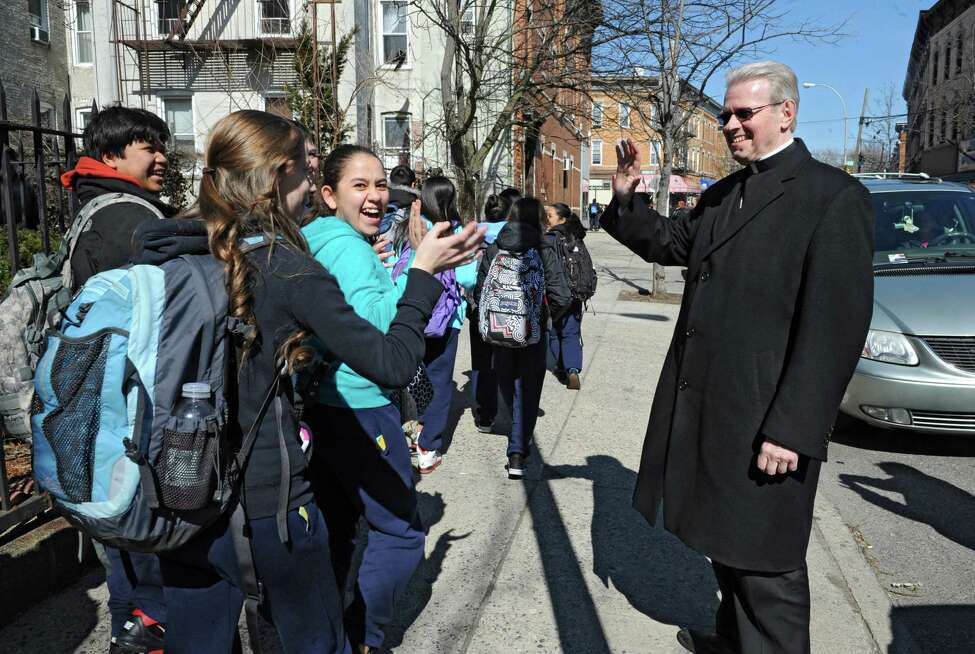 Bishop-elect Edward Scharfenberger waves to students outside St. Matthias Church as school is let out on Friday, March 21, 2014 in Queens, N.Y. (Lori Van Buren / Times Union)