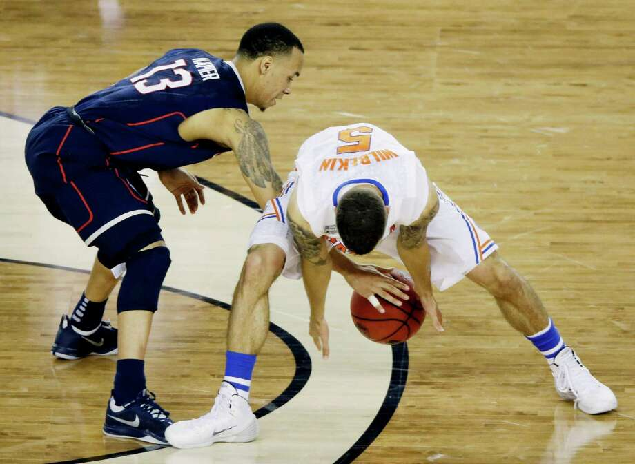 Connecticut guard Shabazz Napier (13) and Florida guard Scottie Wilbekin (5) reach for a loose ball during the second half of the NCAA Final Four tournament college basketball semifinal game Saturday, April 5, 2014, in Arlington, Texas. Photo: Tony Gutierrez, AP / Associated Press